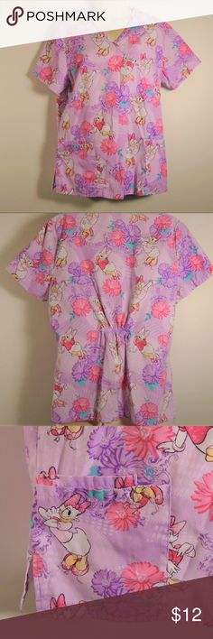 """Disney Daisy Duck Medium Medical Scrub Top Disney Daisy Duck Medium Medical Scrub Top  How fun!! Daisy Duck character set on this lavender/floral background!! Very nice condition with vibrant colors. Double pocket on one side. Elastic cinch in back.  Size: Medium  Measurements (approx): also see pics  Top-      Armpit to armpit- 20""""     Back of collar to hem- 25-1/2"""" Disney Tops Blouses"""