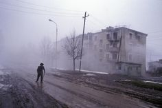 """slugsteak:  """" Nagorno Karabakh. 2005. A man walks past the half-empty apartment blocks of Shushi, a town that was partially destroyed in the Azeri-Armenian war of the early 1990s. Today it remains half-wrecked, and all the previous Azeri residents..."""