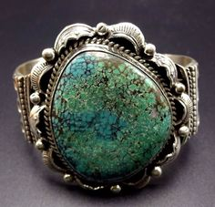 """Applied leaves and hand-stamped raindrops frame the stunning turquoise specimen. MEASUREMENTS: Interior of the cuff measures 5 1/2"""". Measures 2 1/2"""" straight across the widest part of the cuff. Bracelet face measures 2 3/8"""" wide."""