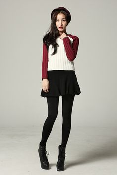 Burgundy and white sweater and black skirt with black tights and black boots