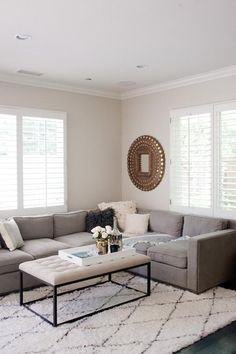 Love this sleek neutral hued living room with gray sectional, black and white diamond print Moroccan rug, tufted iron frame coffee table, and gilded sunburst mirror!