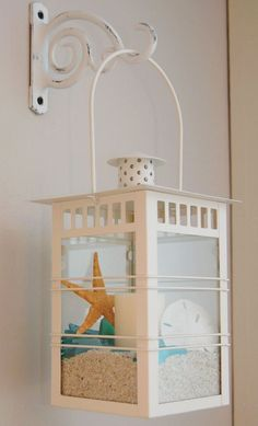 Hanging a lantern with sand, candle and beach finds