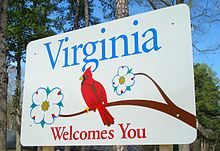 A large square metal sign, mostly white, with the words Virginia Welcomes You in blue and red. In the center a red cardinal bird sits on a branch with two white flowers around it.
