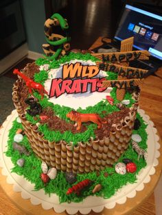 Happy birthday Kyle!!!!  Wild kratts cake animal jungle.  Lot's of questions about this cake, if you need help email me :)  telkinton@sbcglobal.net.  I printed the title off the internet and then laminated it.  Now I have a food safe printer so I guess I would do that instead.  The animals are plastic from target  The sign and number with snake are fondant.  Anyone can do it.    Honestly this is an easy cake, you can do it :)