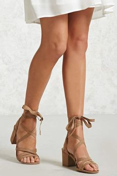 A pair of faux suede heels featuring a strappy upper, open toe, a lace-up ankle wrap design, and a block heel.