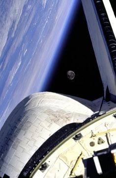 Earth and its Moon are nicely framed in this image taken from the aft windows of the Space Shuttle.