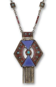 An enamel, blue chalcedony, and turquoise pendant necklace, Theodor Fahrner, circa 1927 - centering an openwork hexagonal panel with two triangular blue chalcedony, red and pink enamel detail, applied wirework and cabochon turquoise, suspended by an elaborate chain of red enamel bars and turquoise accented square links.   © Bonhams 2001-2014