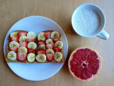 Whole wheat bread with peanut butter, banana and strawberry slices, half a grapefruit, and a glass of almond milk.