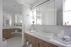 Banheiro grande + acabamentos brancos + armários em madeira clara. Observem que os espelhos garantiram ainda mais amplitude ao espaço. Via: Informacione.