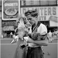 Vivian Maier, New York, NY. I like how comical this image is, its hard to find these unique moments in a city full of the mundane everyday, this is so strange, how a man willingly in feeding the pigeons and allowing them to be on his arms and hand. He looks kind of concerned or worried, but its hard to tell, the lady in the background seems quite amused. The fast shutter speed really captures the decisive moment, having the man and the pigeons all sharp.