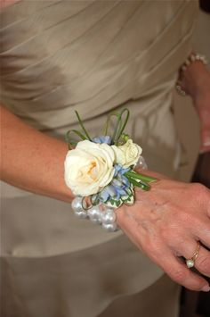beach wedding wrist corsage of ivory roses & blue accents ... For a Wedding Bouquet Guide ... https://itunes.apple.com/us/app/the-gold-wedding-planner/id498112599?ls=1=8 ... The Gold Wedding Planner iPhone App.
