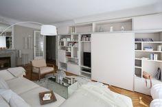 Dans le salon, une grande bibliothéque avec sa porte coulissante apporte du rangement à la pièce. Plus de photos sur Côté Maison http://petitlien.fr/7alw