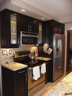 Espresso cabinets with stainless steel appliances and backsplash.