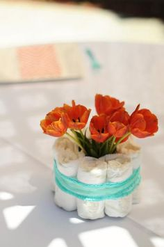 LOVE this diaper + flower baby shower centerpiece idea! (Aqua and Orange Baby Shower from Celebrations & Sweet Creations on HWTM!) Way cute for baby shower decor! Otoño Baby Shower, Bebe Shower, Mesas Para Baby Shower, Fiesta Baby Shower, Diaper Shower, Baby Shower Flowers, Baby Shower Diapers, Baby Shower Parties, Baby Shower Themes