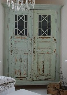 huge, rustic armoire with windows and patchy paint exterior