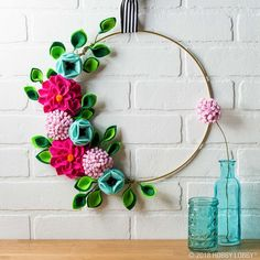 Create an adorable felt flower hoop wreath! We'll show you how to make simple flowers and leaves out of felt.