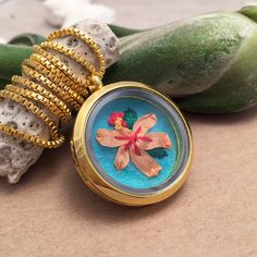 How pretty and unique is this hand embroidered hibiscus necklace? It's a silk ribbon embroidered flower set in a shiny glass locket. And you can see the stitching on the back! It's totally handmade and both sides are lovely. https://www.etsy.com/listing/260763725/gifts-for-women-embroidered-necklace