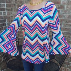 Bell Sleeve Chevron Top Free flowing, cute chevron top with bell sleeves, beautiful colors, new with tag!  100% polyester.  Machine wash cold.  Length: about 29 inches.  Bust laying flat: 20 1/4 inches.  Sleeve length from shoulder seam:  23 3/4 inches.  Could possibly fit a medium or large since it is loose and flowy. Cacia Tops Blouses