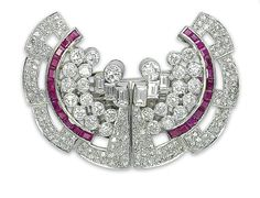 AN ART DECO RUBY AND DIAMOND DOUBLE CLIP BROOCH   Each clip designed as a stylized pavé-set diamond fan enhanced by a line of calibré-cut rubies and a cluster of circular and baguette-cut diamond collets, mounted in platinum and gold, 1930s, 6.0 cm