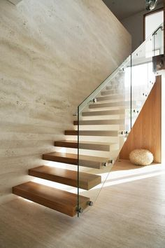 Cantilevered blackbutt staircase with a glass-and-steel balustrade. Raw travertine tiles create a feature wall Glass Stairs Design, Home Stairs Design, Stair Railing Design, Cantilever Stairs, Staircase Handrail, House Staircase, Staircase In Living Room, Spiral Staircases, Glass Handrail