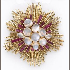 A retro moonstone, ruby and eighteen karat gold brooch, Sterlé. A sunburst motif brooch set with moonstone cabochons of various shapes and sizes, accented by baguette-cut rubies, to twisted gold sprays; signed Sterle, Paris, reference #A281.