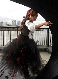 """What You'll Need: Dad's old bandanna, long-sleeved white shirt, dad's suit vest, black tutu and red-ribbon.  Tip: Pull some hair from underneath the bandanna and braid it for the perfect """"sailor's life for me"""" touch."""