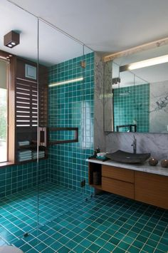 Go with color, like these teal tiles covering the floor and the shower too. Reminiscent of the ocean, this option sets the tone for a gorgeous, super chic and a bit Asian-inspired space for you or your guests to enjoy.