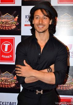 Tiger Shroff covers his long hair with a hat while posing on the red carpet in a black shirt and black trousers. via Voompla.com