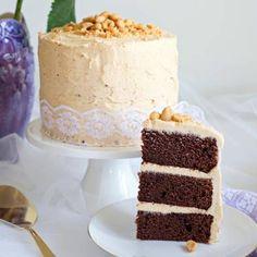 Den höga choklad- och jordnötstårtan blir extra vacker med några jordnötter på toppen och ett spetsband runt om.