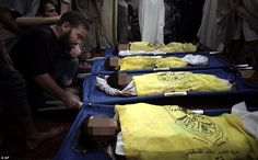 Inconsolable Palestinians mourn over the dead bodies of four boys from the same family, who were killed by an Israeli airstrike on a beach in Gaza