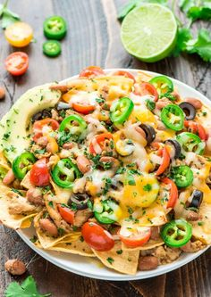 Loaded Crock Pot Chicken Nachos recipe — so perfect for parties, football games, Cinco de Mayo, or even a quick weeknight meal. The chicken is fall-apart tender and the toppings are irresistible! @wellplated #slowcooker #crockpot