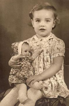 1950 Vintage Photo - Adorable Gisella in a cute dress & wool tights, holding her baby doll. #littlegirl