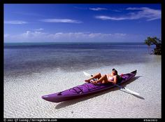 Woman reclining in kayak on shallow waters,  Elliott Key. Biscayne National Park (color)