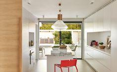 El mobiliario integral de la cocina es un diseño de Vincent Coste, al igual que el taburete rojo. Grifería de Grohe. Sobre la encimera de la isla, piezas de cerámica blanca, de Alessi