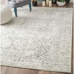 Bring antiqued inspiration and a patterned foundation to any room with this area rug. Machine woven in Turkey from 100 percent polypropylene, this synthetic rug's .25-inch pile is embellished with a Persian-inspired, faded motif in an ivory and gray color palette. Use this sophisticated area rug as a warm anchor to a contemporary aesthetic in your living room. Paint paneled walls white with matching trim to contrast wood floors. Roll out this rug, and then top it with a sleek glass coffee…