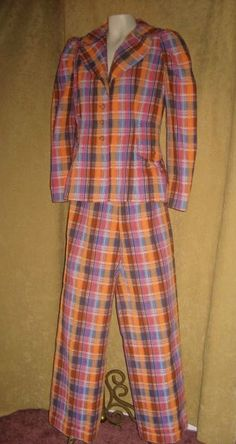 """This vintage sixties plaid suit has bright colors in orange, hot pink, dark blue, turquoise blue, and white. The jacket is lined in orange cotton.    The suit was handmade and the jacket buttons down the front. The pants have wide legs and a metal zipper in front. The pants have a 2"""" cuff. There is a faux pocket on each side of the jacket. The jacket also has pointed yoke in back and center pleat. The pants are not lined. The seersucker pant set is cotton.    The measurements are 38""""…"""
