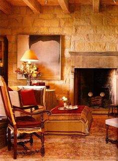 the thread bare antique carpet in the great room is gorgeous with the sandstone walls and the red fabrics, john saladino