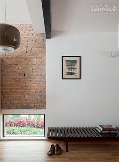 A sutil transição entre sala e cozinha e seria imperceptível não fossem a viga metálica (necessária devido à demolição de uma parede) e a superfície de tijolos descascados. Baixa, a janela deixa a vista do jardim e a luz natural entrarem, sem expor o interior da casa.