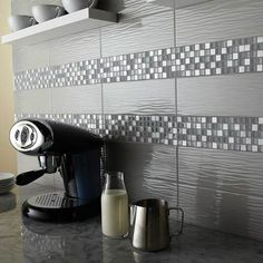 This photo features Urban Canvas™ 4 1/4 x 12 3/4 Wave Tile in Light Smoke Gloss and Morello™ Mosaics in Moonstone. Assorted trim sizes are also available.