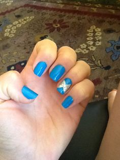 Sally hansen blue me away nail polish with gold sparkle bow and silver gem