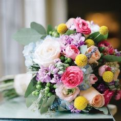 Can't decide on a color? Use them all! - What a beautiful and colorful bridal bouquet with peach and blush roses, pink ranunculus, blue hydrangea, lavender stock, yellow craspedia, green hypericum, and seeded eucalyptus.