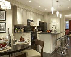 Appliances: White Kitchen Cabinet With Black Appliances. black kitchen appliances. black refrigerator. black stove. white kitchen cabinet. black kitchen island. dark countertop. metal barstools. round dining table. mini glass pendant light.