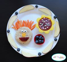 carrot top guy: peanut butter sandwich cut into circle, matchstick carrots for hair, apple mouth, cheese nose and candy eyes.    silicone muffin liners filled with unsweetened berry applesauce with sprinkles on top and another filled with blueberries.    apple slices and blueberries for garnish.
