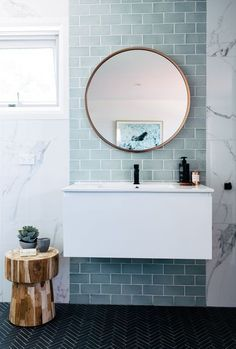 blue green subway tiles with marble, round mirror, black faucet, wooden side table stool