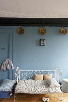 Une chambre style années 30 Photo : Nicolas Millet Dans la chambre d'enfant, éclairée par une série d'appliques de bateaux, un lit en fer forgé, le tout chiné aussi.