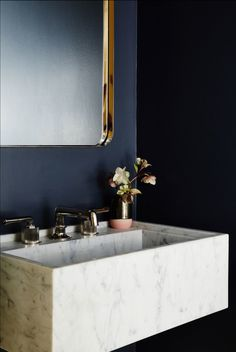 This marble sink sits beautifully next to navy walls. Via Architectural Digest