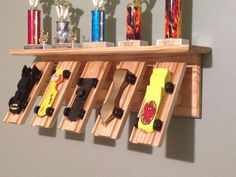 Derby Car Display, Wall Shelf, Pinewood, CubScout Derby Shelf, Five Car Trophy Shelf, Natural Finish. A great way to display cars & trophies!  The shelf measurement is 28wide x 5-1/2deep. Overall measurement is 28 x 9 x 10-1/2 Has key hole hanger slots so it will fit flush against the wall.  Your Scout can show off his Derby Cars, Trophies and Pictures on this shelf while keeping them safe and off the floor. This Shelf will be made from solid pine and has a clear finish to protect and bring…