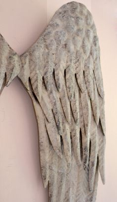 """These gorgeous distressed angel wings have flown in just in time for the holidays! The grey finish has been distressed for a rustic look. Perfect for industrial or rustic style decor.. A lovely wall hanging near a crackling fireplace with stockings, or even as part of a door decoration! Such a versatile piece will enhance your cottage home year round. Comes ready to hang.  Ships immediately otherwise please allow 2-3 prior to shipment weeks if not in stock. 23""""w x 24""""t"""
