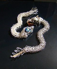 Dragon bracelets, modified Dragonback weave in 18g, 9mm OD jewelry jump rings, wire wrapped heads and tail in 18g and 28g copper colored wire, glass Czech be...