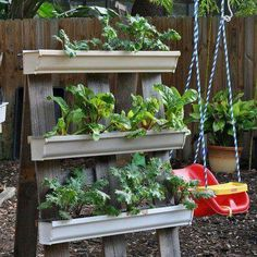 Planter made from a stand with gutters for planting. I have seen this done on a garage wall on the outside and on fencing. What a great idea!
